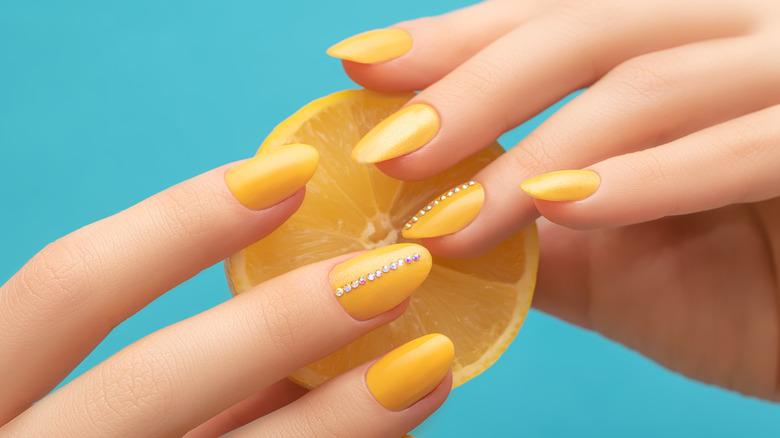 Hands with yellow nail polish