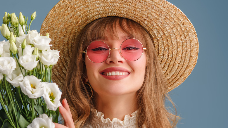Woman with round pink sunglasses and a straw sunhat