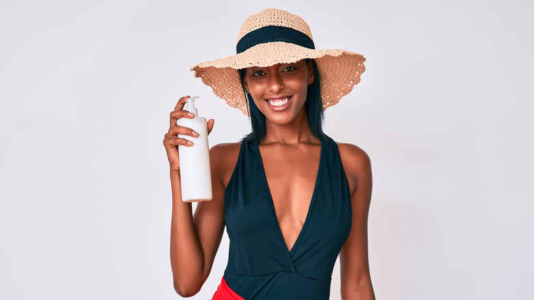 Woman in swimsuit holding bottle of sunscreen