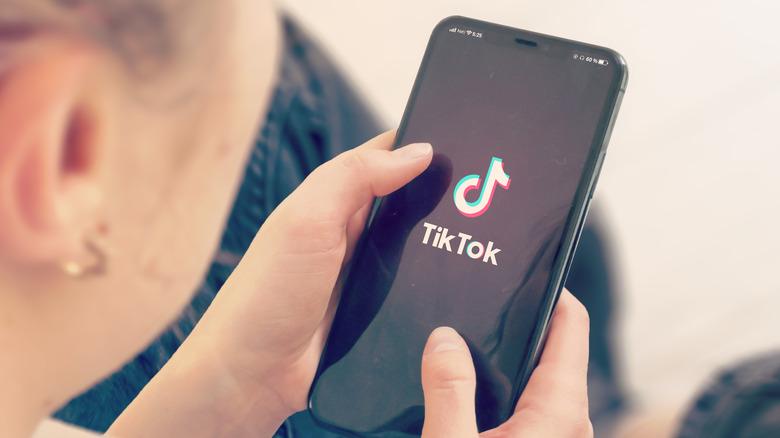 A woman loading TikTok on her phone