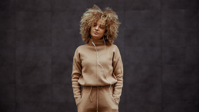 girl in tracksuit standing with hands in her pockets and listening music