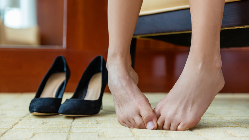 A woman waiting to try on a pair of black heels