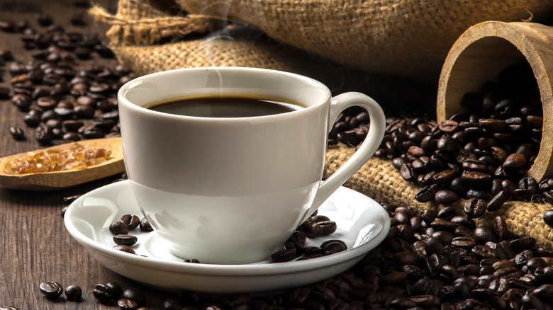 A cup of coffee around beans