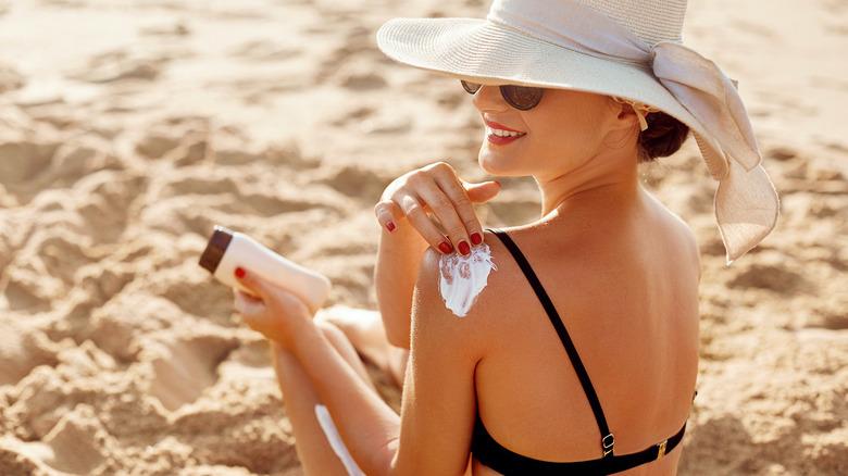 woman wearing hat at beach applying cream