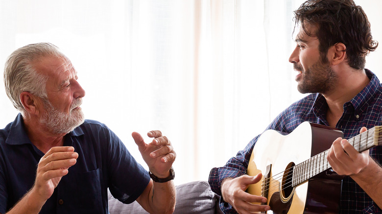 Annoyed senior father with his grown son playing guitar on the couch