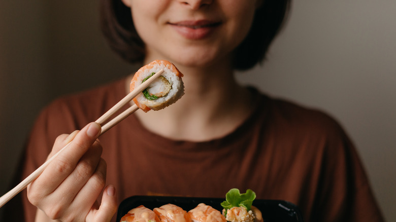 woman holding chopsticks
