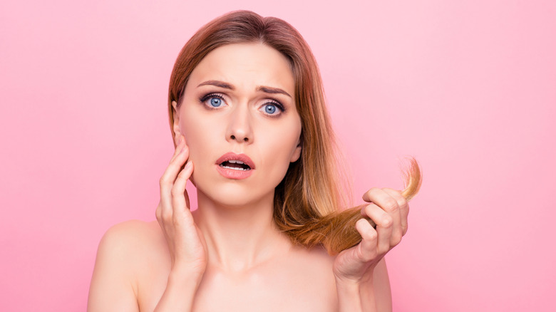 Woman holding her over processed hair