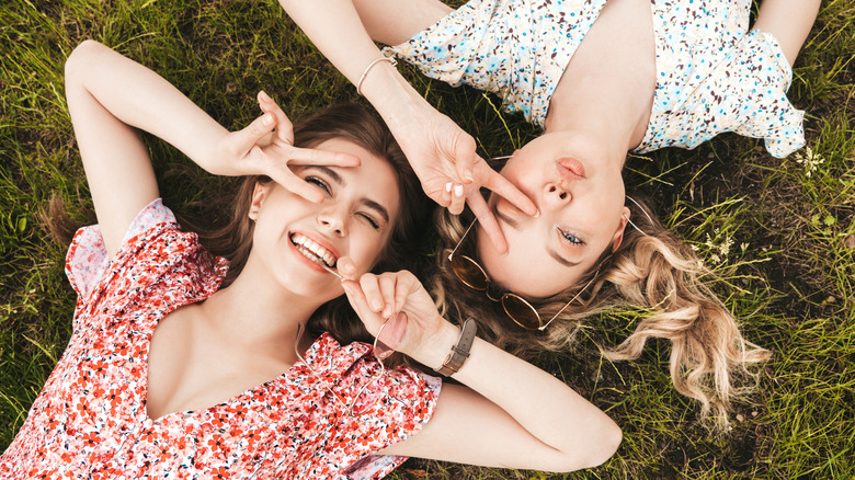 two young woman laying on the grass in summer dresses