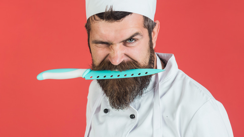 Chef holding knife in teeth