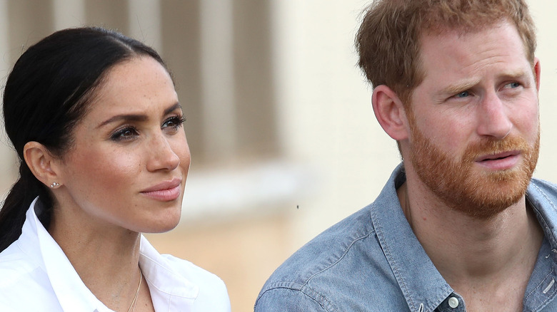 Meghan and Harry listen during an interview