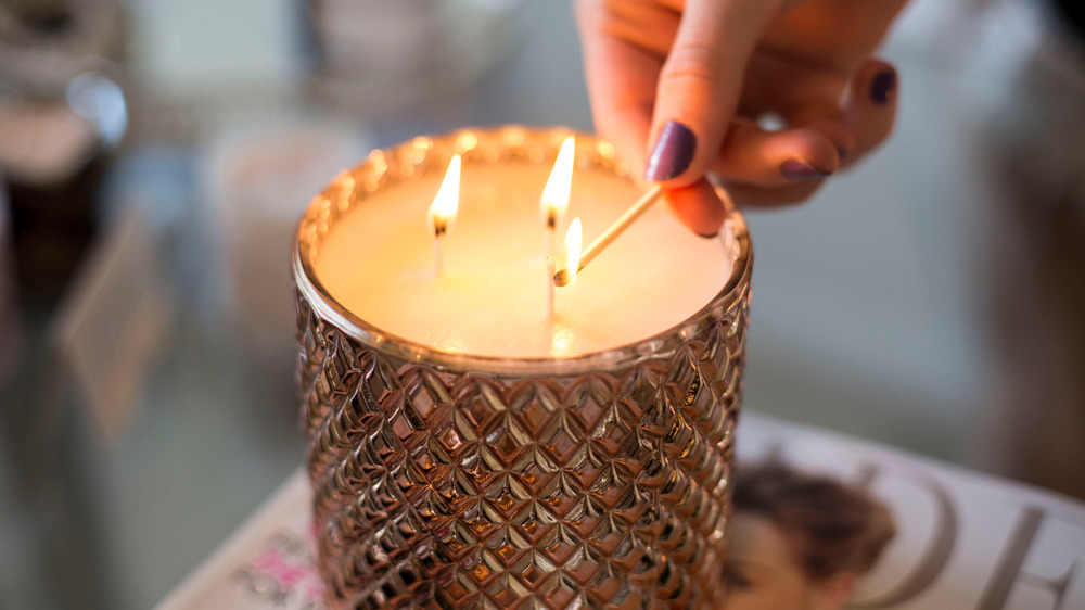 A hand with dark painted fingernails lights a three wick candle in a metallic holder