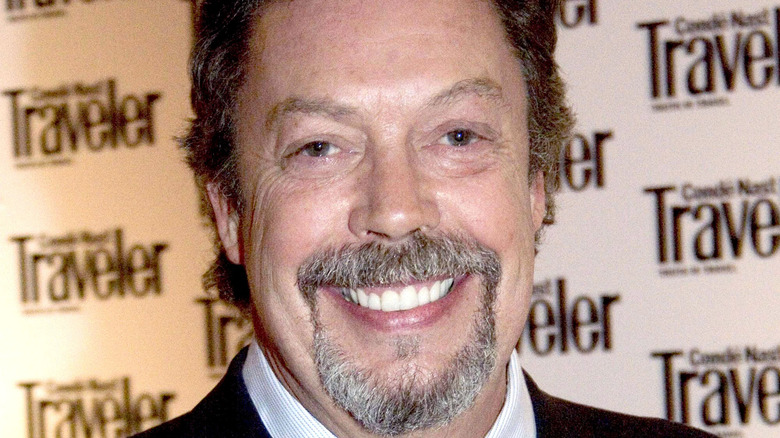 Tim Curry smiles on the red carpet