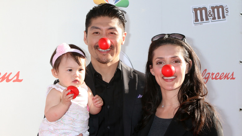Brian Tee with wife and daughter wearing red noses at event