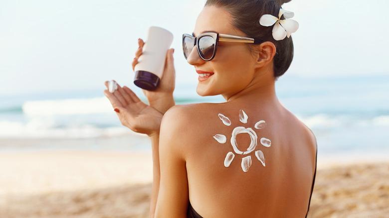 Woman on a beach wearing a black bikini and a sunhat applying sunscreen.