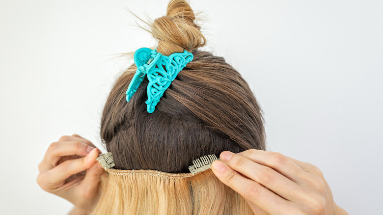 blonde person clipping in extensions