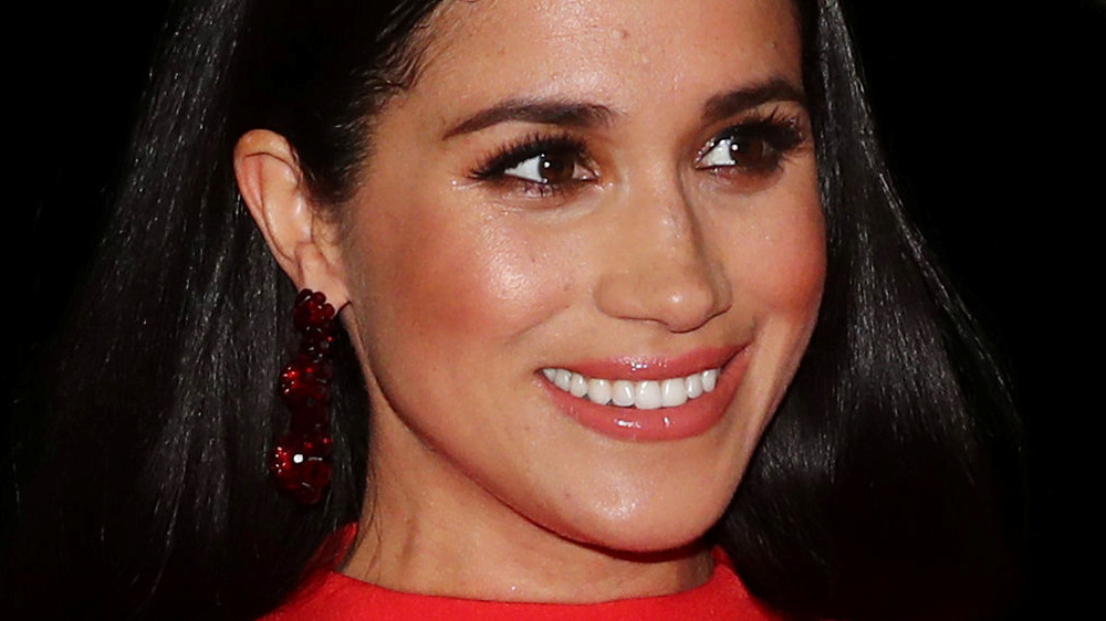 Meghan Markle smiling in red