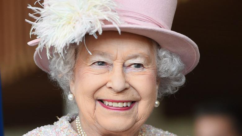 Queen Elizabeth II smiling in pink hat