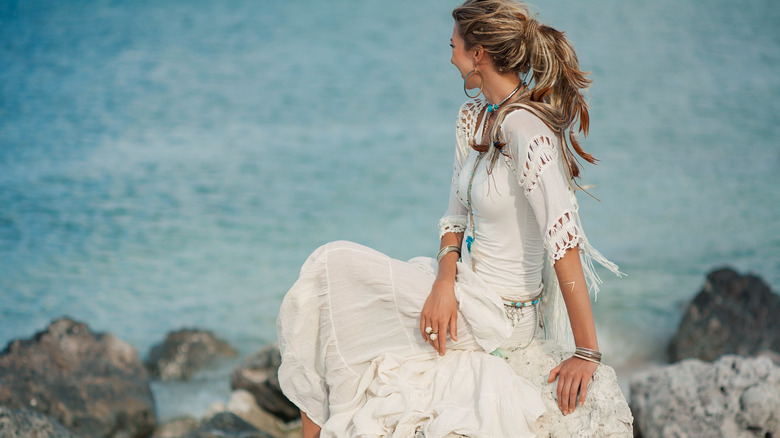Bohemian woman in tiered dress by the shore
