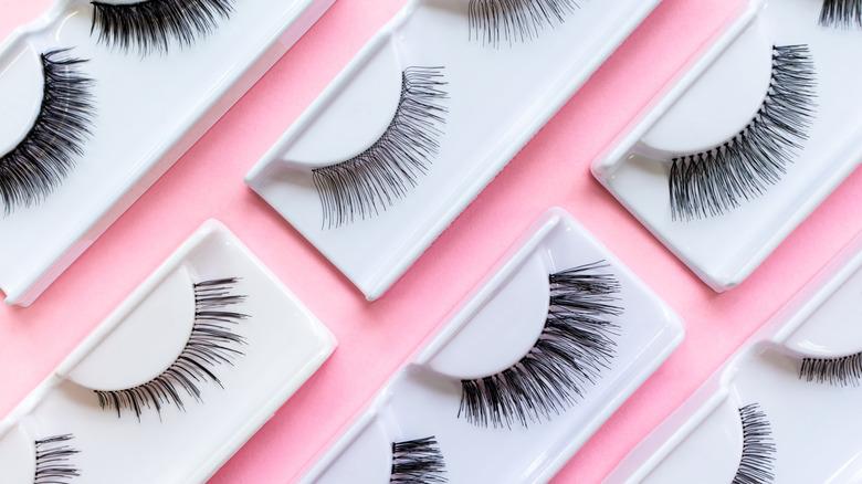 Several sets of false eyelashes on a pink background.
