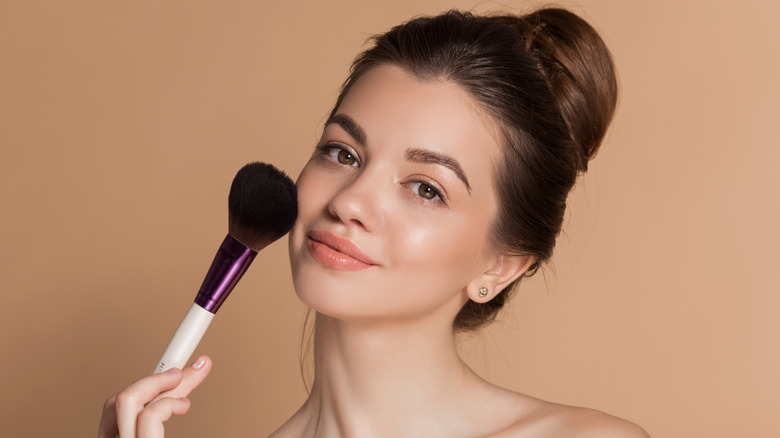 Young woman with her brunette hair in a bun holding a large makeup brush on her cheek.