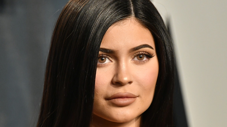 Kylie Jenner poses with a closed-mouth smile.