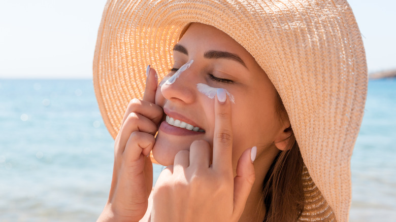 Woman on the beach applying sunscreen to her face