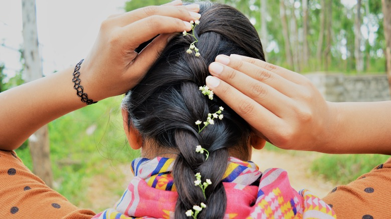 Brunette putting baby's breath flowers into her French braid.