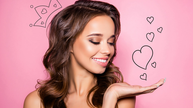 Charming brunette woman with a cartoon crown and hearts near her face