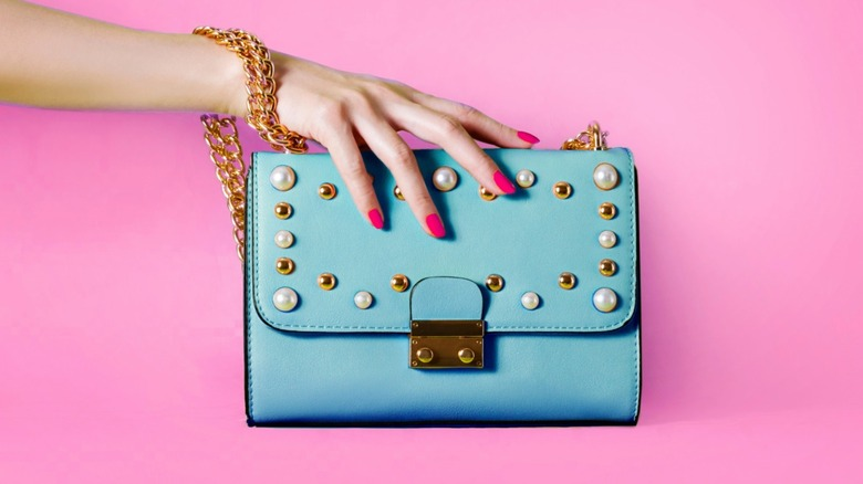 woman holding turquoise purse pink nails