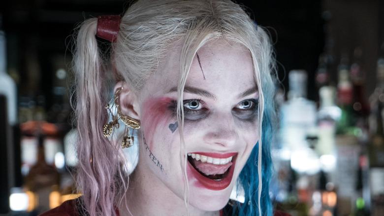 Margot Robbie's Harley Quinn grinning at a bar