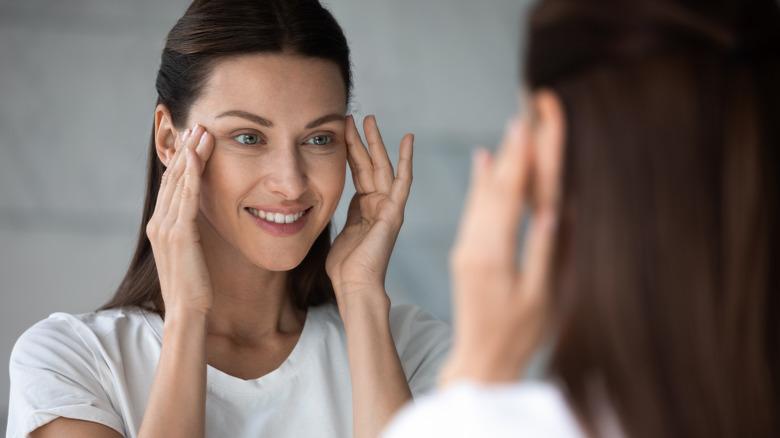 Woman applying eye cream in the mirror