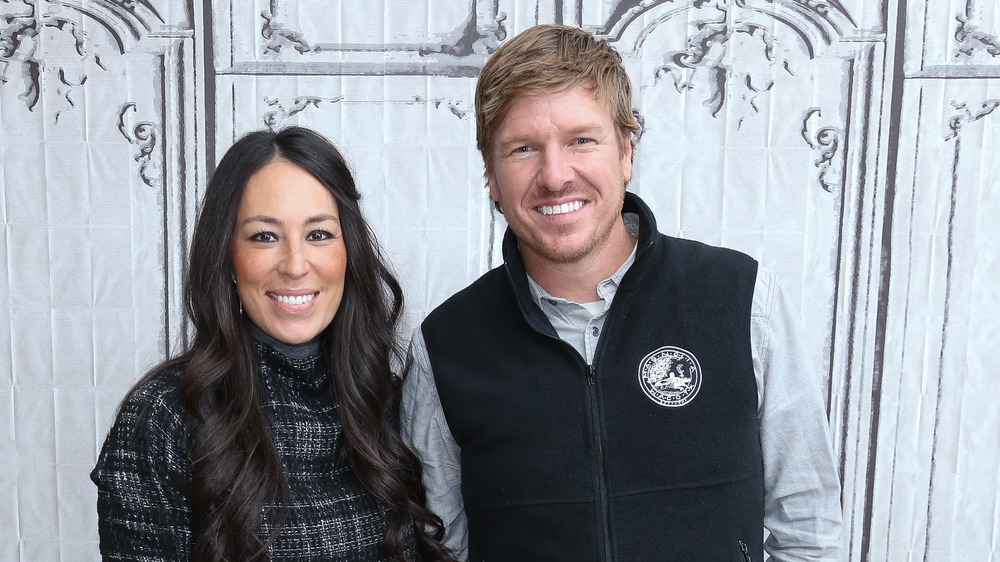 Joanna and Chip Gaines by a white wall