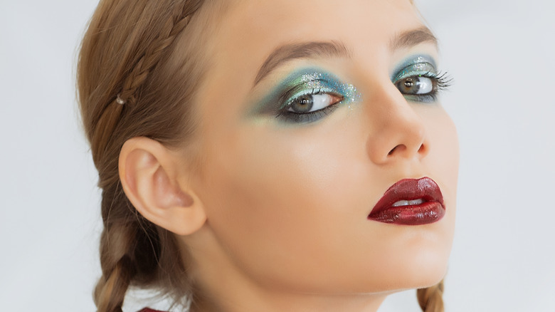 Woman with dramatic eyeshadow and a bold lip.