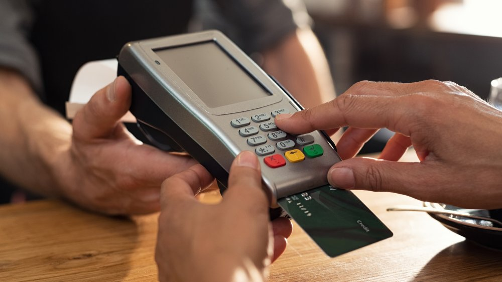 Hand touching credit card machine