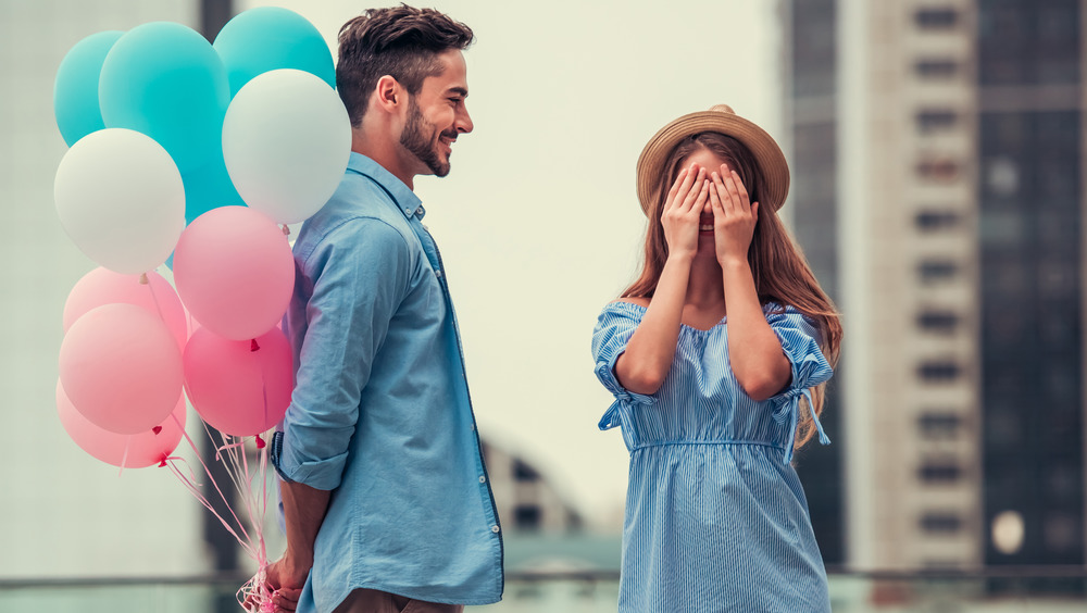 Man with balloons surprises woman