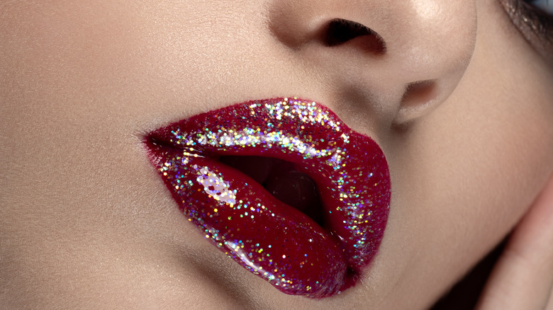 Red glitter lip gloss on lips