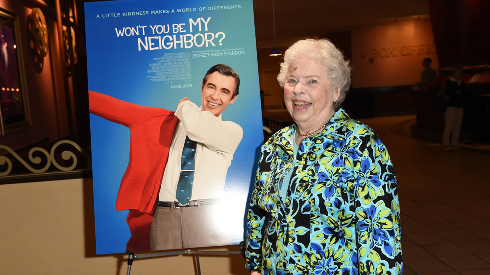 """Mrs Joanne Rogers next to a """"Won't You Be My Neighbor"""" poster"""