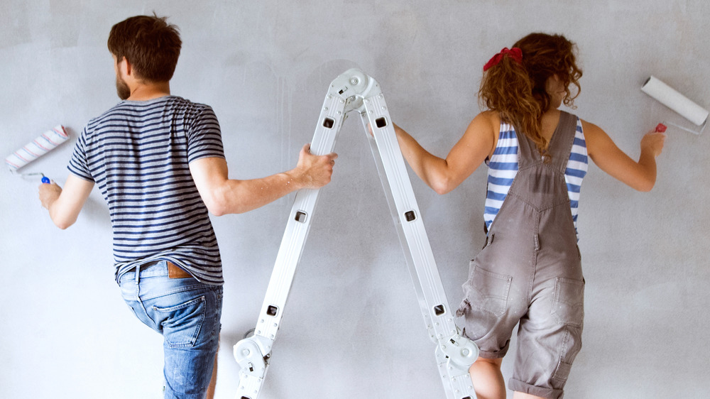 Man and woman standing on a ladder painting.