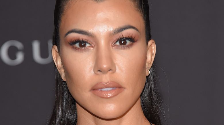 Kourtney Kardashian posing with pale lipstick