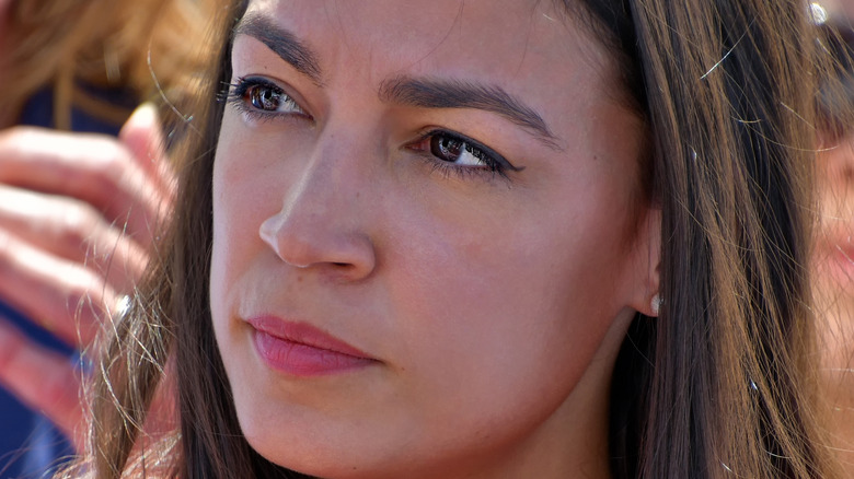 Alexandria Ocasio-Cortez looks off to the side with a pensive glance.