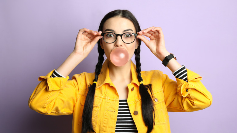 young woman with braids blowing bubblegum