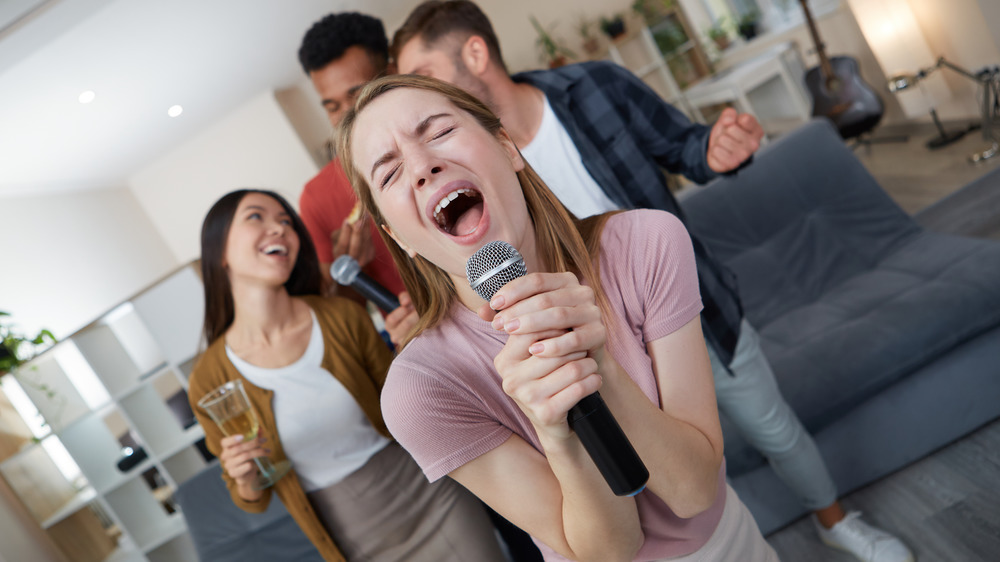 Woman singing karaoke at party
