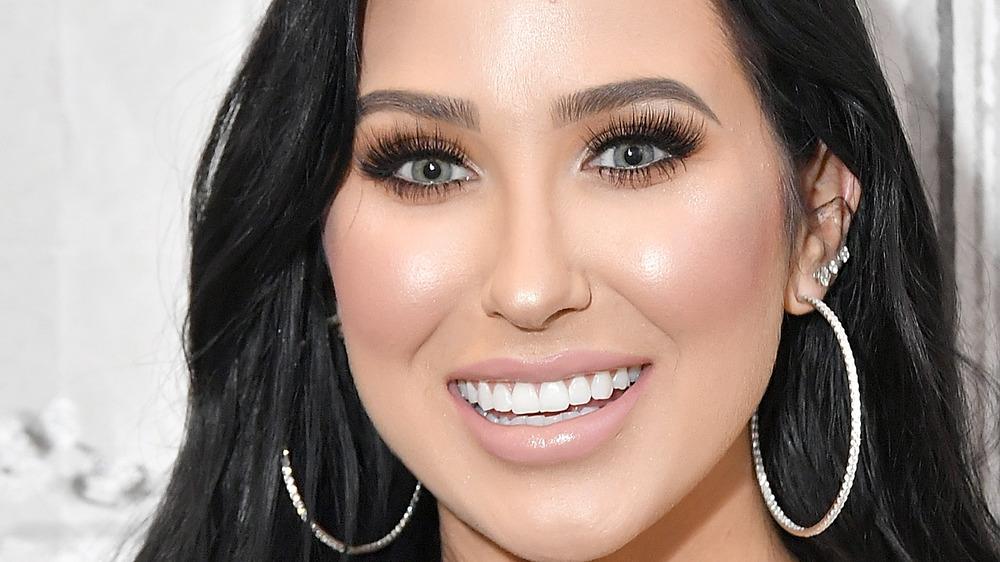 Jaclyn Hill smiling in hoop earrings