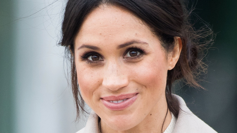 Meghan Markle smiles with her hair pulled back