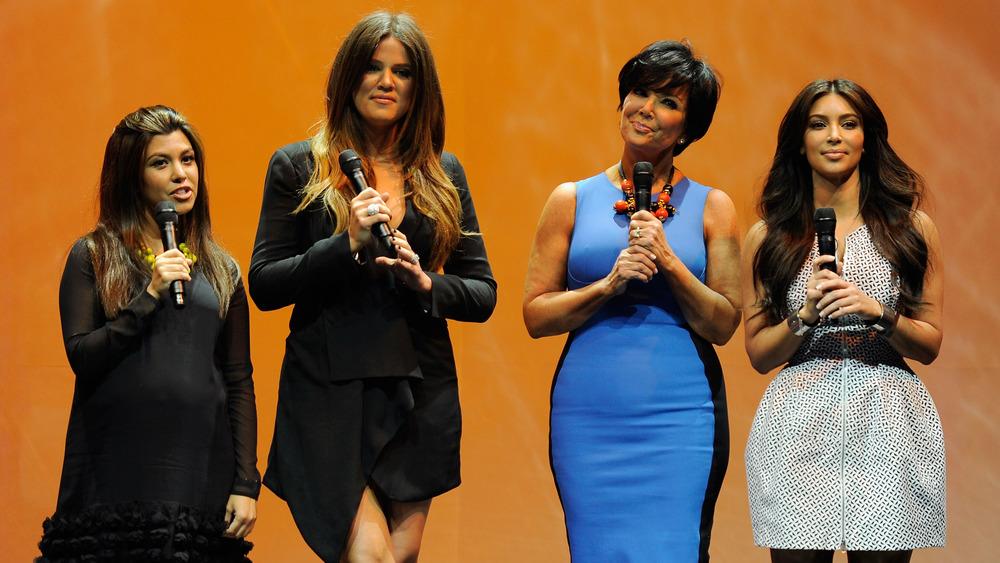 Kourtney, Khloe, and Kim Kardashian with Kris Jenner on stage