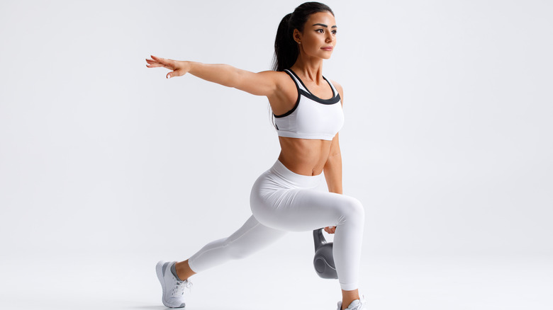 Woman in leggings and sports bra doing lunge