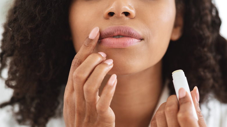 Woman applying lip balm, holding lip balm stick and applying with her finger