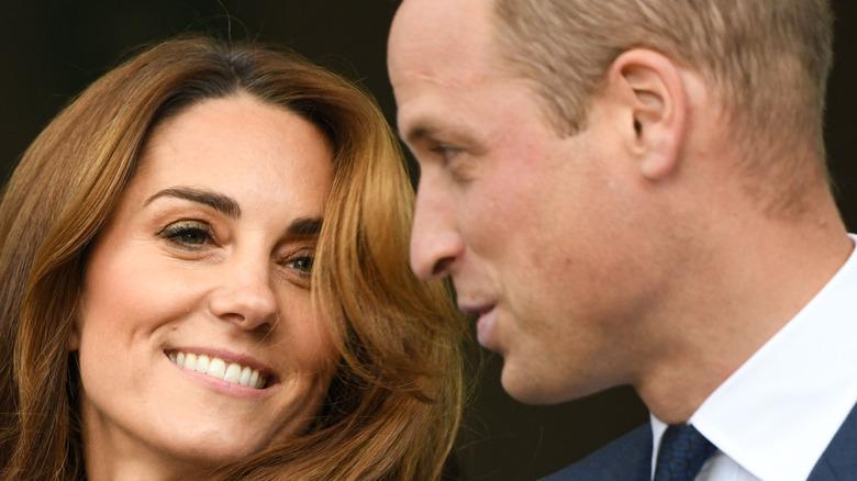 Kate Middleton smiling while Prince William talks