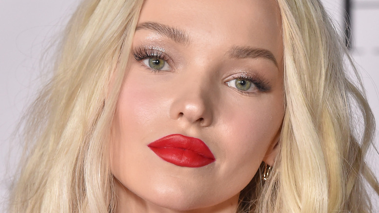 Dove Cameron wearing red lipstick and posing for a picture