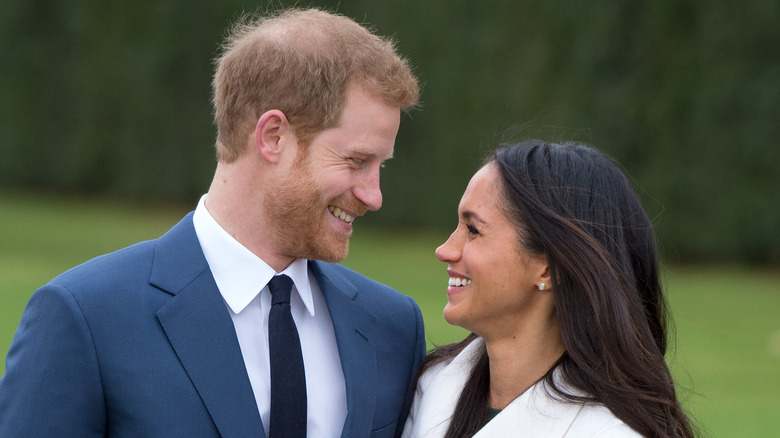 Prince Harry and Meghan Markle grinning at each other